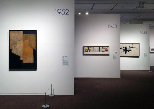 画像: ホワイトの壁。1年1作家1作品ずつ一つの壁面に展示されています。 作品の壁面の間にブルーの作家プロフィールの壁面が並びます。 photo©cinefil