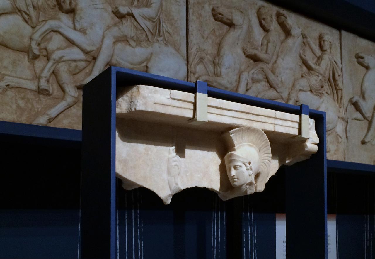 画像: 手前:アテナの浮彫り 前5世紀後半 大理石 アテネ考古学監査局蔵 奥:パルテノン神殿の西面フリーズ(複製) 5面 (原品):前442〜前438年 大理石 アテネ、アクロポリス博物館蔵 photo©cinefil