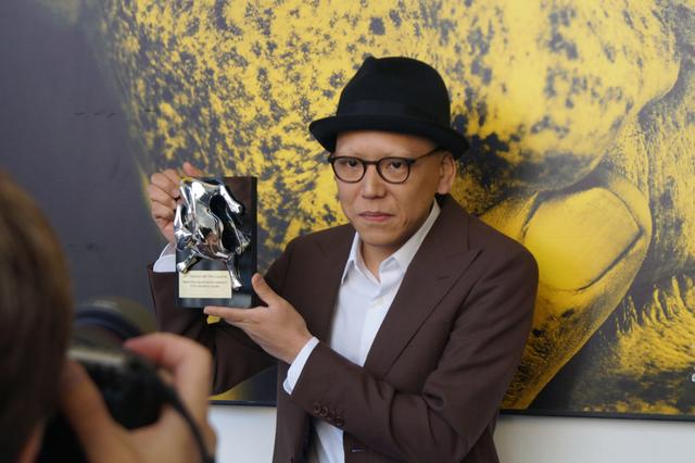 画像: トロフィーを持ち取材に答える真利子哲也監督