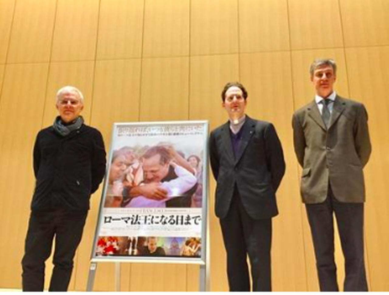 画像: ポスター左がダニエーレ・ルケッティ監督、ポスター右よりレンゾ・デ・ルカ神父、ホアン・アイダル神父