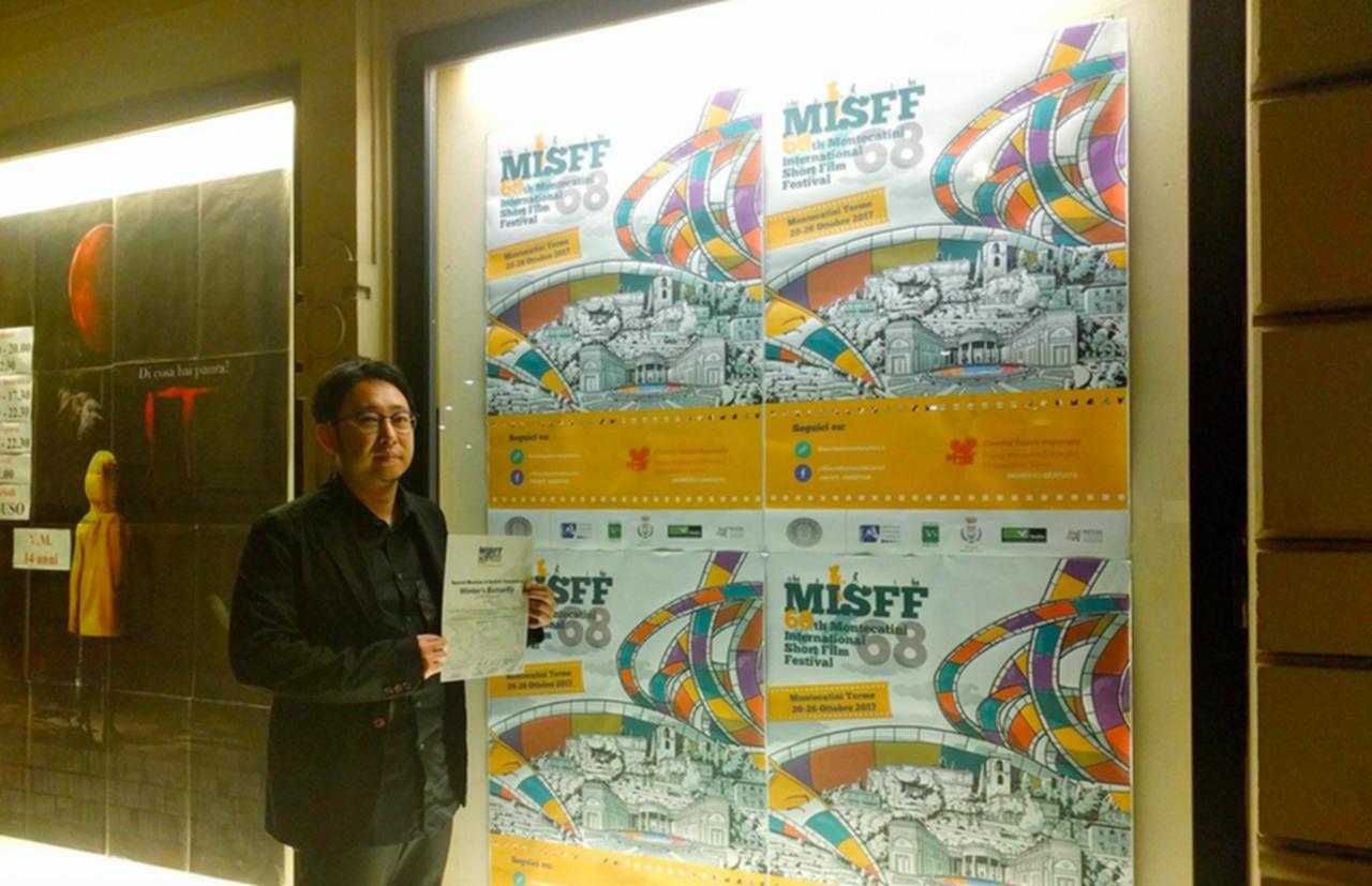 画像: 遠山昇司監督 映画祭ポスター前で賞状を見せる