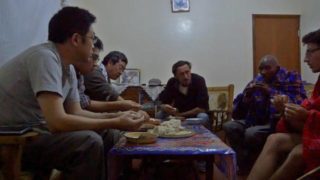 画像: 食事をする研究者たちと家主らしきセンテロさん