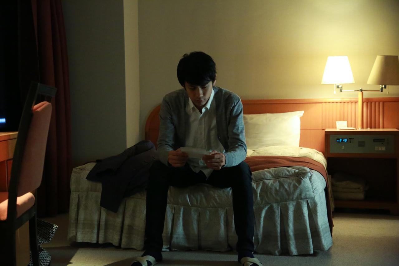 画像: ホテルで写真を見つめる樹(馬場良馬) (c)『一人の息子』製作委員会