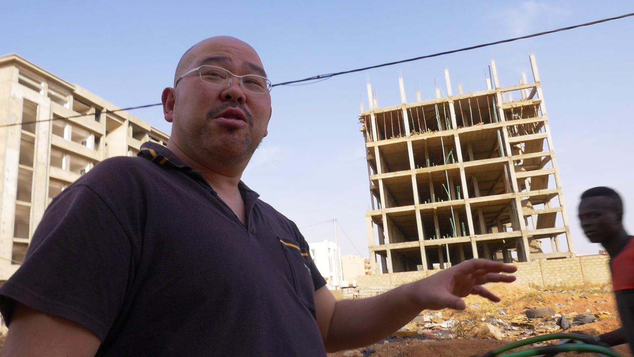 画像: ワガドゥグの街を歩きながら解説をしてくれる清水さん