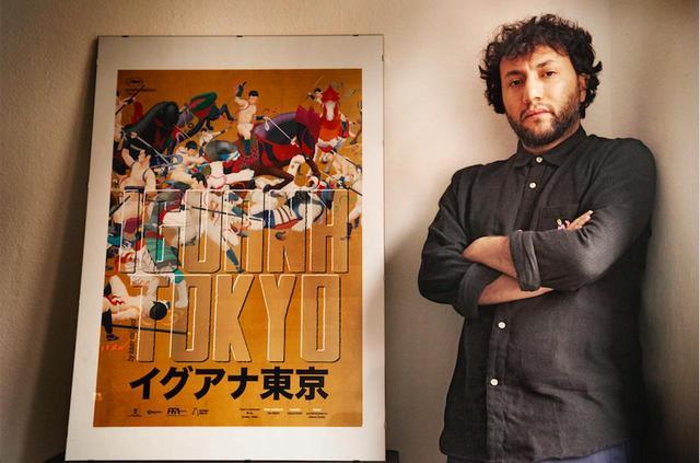 画像: イメージポスターと並ぶカアン・ミュジデジ監督
