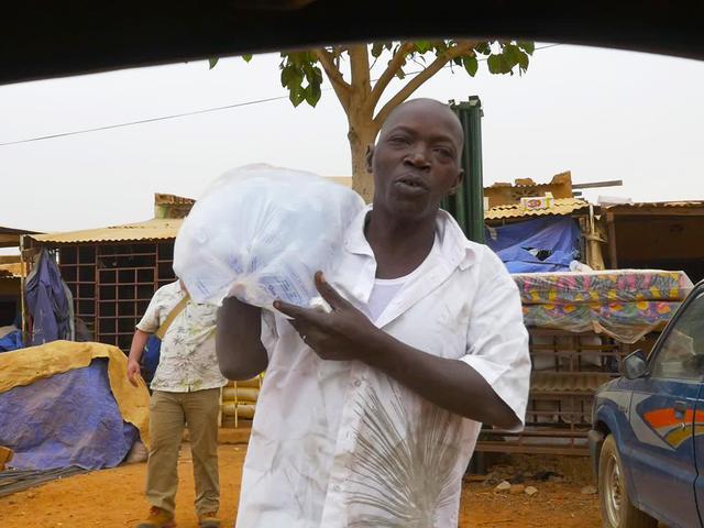 画像: 買い込んだ大量の水を運ぶドライバーのアブドゥルさん
