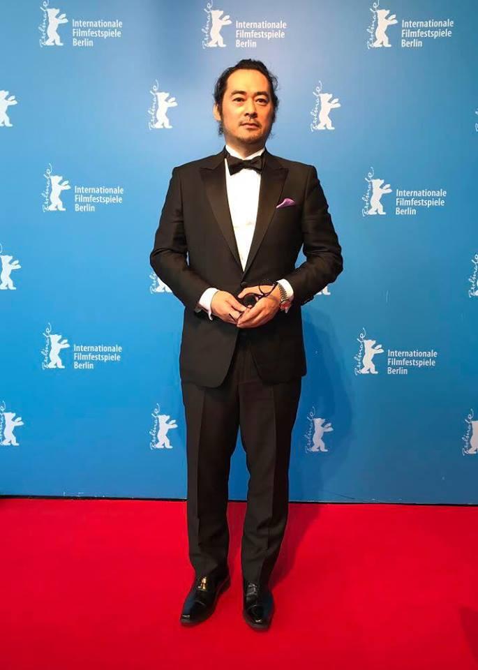 画像: 富名哲也監督(今年2月ベルリン国際映画祭にて) タキシードなど衣装協力 TAKEO KIKUCHI