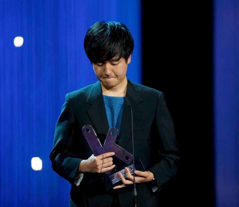 画像: 受賞トロフィーを持ち壇上に立つ奥山大史監督