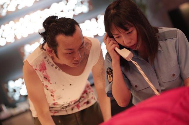 画像: ▲ヤクの売人ウォンと詩織の2ショット。一体詩織は誰に電話中? ©2018 SOULAGE