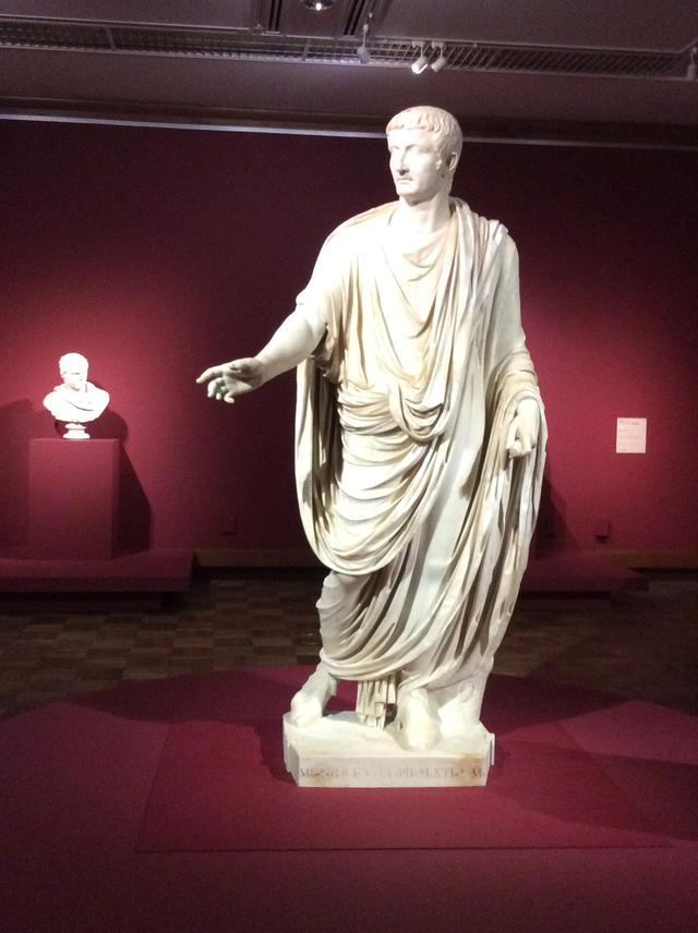 画像: 手前:《トガをまとったティベリウス帝の彫像》 イタリア、カプリで発見(身体のみ) 40年ごろ(頭部); 50−60年(身体) 大理石 高さ 230cm 奥:《胴鎧をまとったカラカラ帝の胸像》 イタリア、ティヴォリで1769年(?)に発見 212−217年(頭部) 大理石 高さ 66cm photo©︎cinefil