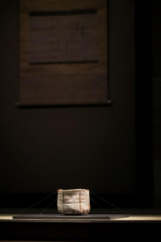 画像: 志野茶碗 銘「卯花墻」 安土桃山時代 16〜17世紀 旧・江戸冬木家伝来 明治20年代半ばより室町三井家に 今年は茶室「如庵」(織田有楽斎 作)の再現コーナーに展示。「如庵」は有楽斎が隠居先だった京都・建仁寺の塔頭、正伝院に建てたものだが、明治維新で正伝院が廃寺となり、後に三井家に買い取られて東京、続いて大磯に移築された。戦後の財閥解体で名古屋鉄道の所有になり、現在は犬山市の名鉄犬山ホテルに。国宝。 背後の軸は、後水尾上皇宸翰の和歌懐紙「深山鹿」 江戸時代18世紀 個人旧蔵