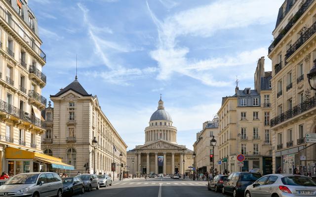 画像: 正面がパンテオン。このスフロ通りを逆向きに歩くとリュクサンブール公園にぶつかる。通りの名称はパンテオンの設計者ジャック・ジェルメン・スフロ(1713-80)に由来。スフロは「パリの国王の建築物の監督官」であった。パンテオンの左手にサント=ジュヌヴィエーヴ図書館、左斜め後ろにはサン=テチエンヌ=デュ=モン教会が立つ。右斜め後ろのエストラパード通りにはベッケル『エストラパード街』(1953)で夫の浮気を知って家を出たフランソワーズ(アンヌ・ヴェルノン)が独り暮らしを始める下宿がある。そこで出会うのがボヘミアンの音楽家(ダニエル・ジェラン)だ。