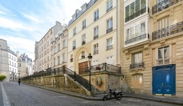 画像: マルブランシュ通り。右端が『昼下がりの情事』(1957)でアリアーヌ(オードリー・ヘプバーン)が私立探偵の父(モーリス・シュヴァリエ)と暮らすアパルトマン。ホテル・リッツから夢心地のまま帰宅したアリアーヌはチェロを納めた大きな楽器ケースを抱えてこの青いドアから入り階段を上っていく。『ミッドナイト・イン・パリ』ではガートルード・スタインの住むアパルトマンは階段を上がってすぐの建物という設定。