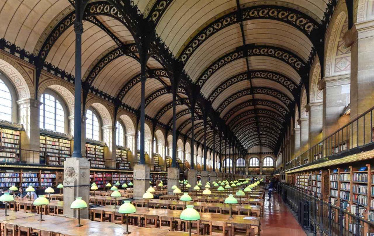 画像: サント=ジュヌヴィエーヴ図書館(1843)の2階閲覧室。平行する2つのヴォールト天井を鋳鉄でつくられたアーチと鉄柱が支える。長辺方向いっぱいに延びた大天井とそれを支える繊細優美な鉄のデザインのコントラストが素晴らしい。設計者のアンリ・ラブルースト(1801-75)は旧国立図書館でも閲覧室をデザインしているが、彼のこのもうひとつの代表作は、ミシェル・フーコーが通い日中こもって作業をしたことでも知られる。