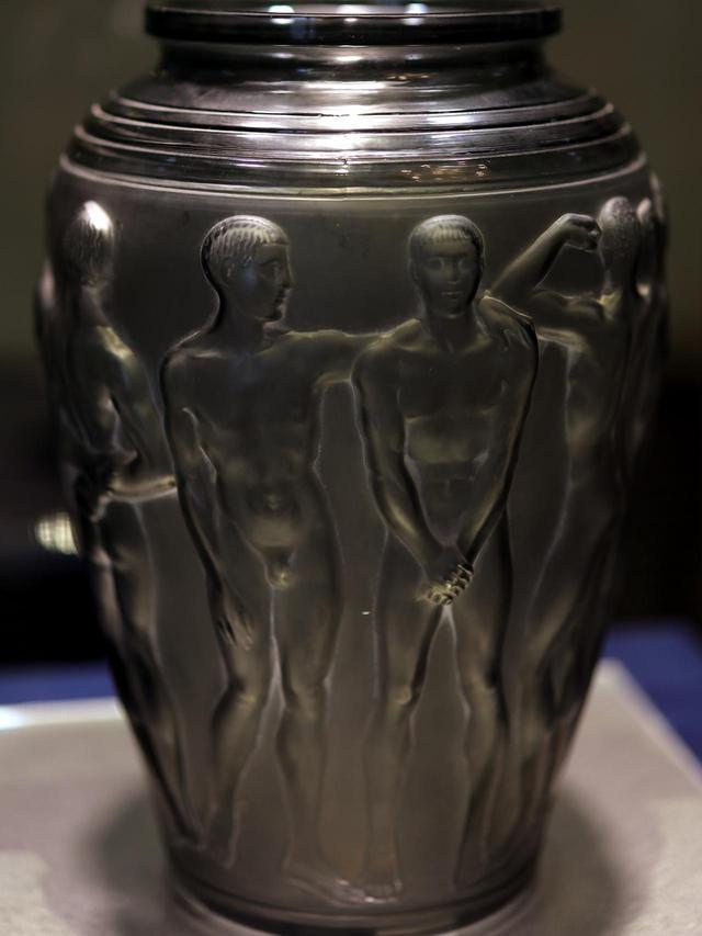 画像: ルネ・ラリック 花瓶「パレストル」1928年 メタリックな質感に見えるが、金型の中にガラスを吹いて成形した濃いグレーのスモーク・ガラスにサティネ加工を施したもの。さらに白系の顔料のパティネで輪郭線と凹凸を強調して立体感を浮き立たせている。北澤美術館蔵