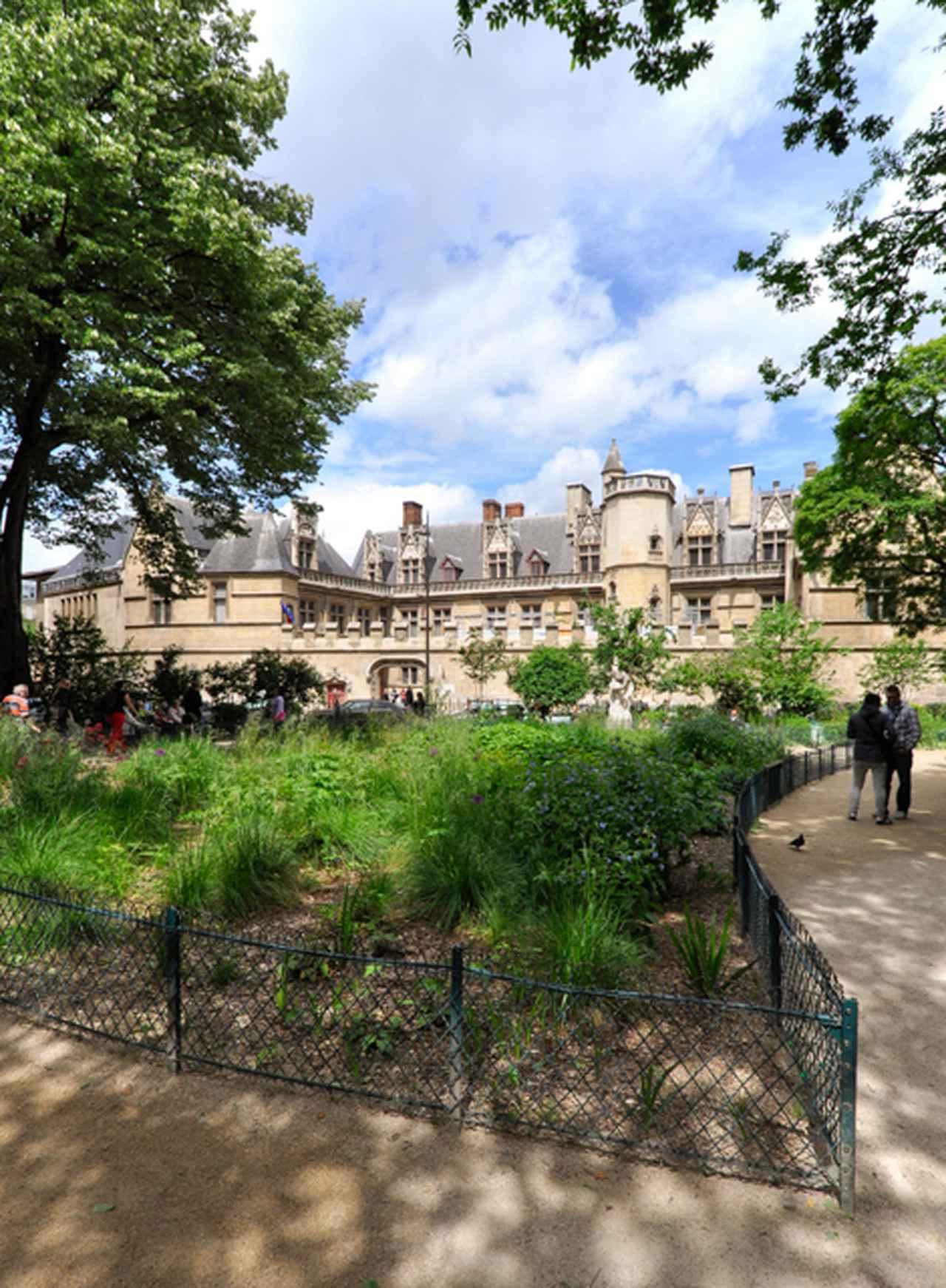 画像: 公園越しにクリュニー中世美術館を見る。建物の裏手の一角には中世に使われていた薬草や野菜を育てる庭がある。この手前の公園もそれと関連したものかもしれない。この建物の左(西)側にテルム跡がある。