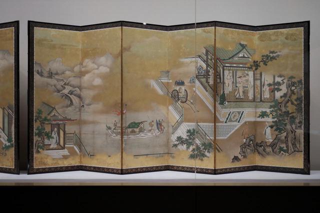 画像: 狩野探幽 「両帝図屏風」江戸時代 寛文元(1661)年 右隻 主役の黄帝の宮廷は右端1/3に、やや遠ざかった中景に描かれ近景には岩と樹木が。あわせて黄帝が発明して民衆を助けたとされる車と舟がさりげなく描き込まれているが、絵の中心となるのはその舟の浮かぶ池と彼方に連なる山河