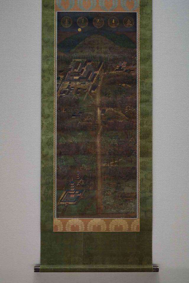 画像: 春日宮曼荼羅 鎌倉時代14世紀 根津美術館蔵 重要美術品 最上部・奥に春日山と、手前に御蓋山で、その麓の左に春日大社の本殿と本殿を取り囲む回廊など。右に春日若宮。中心の垂直の線が春日大社の参道で、右下に描かれている仏塔は神仏習合の時代にかつてあった春日大社の五重塔(今も奈良国立博物館の構内に礎石が残る)。 最上部は右端に若宮の本地仏・童形文殊菩薩。そして右から第一殿の本地仏・釈迦如来、第二殿・薬師如来、第三殿・地蔵菩薩、第四殿・千手観音菩薩