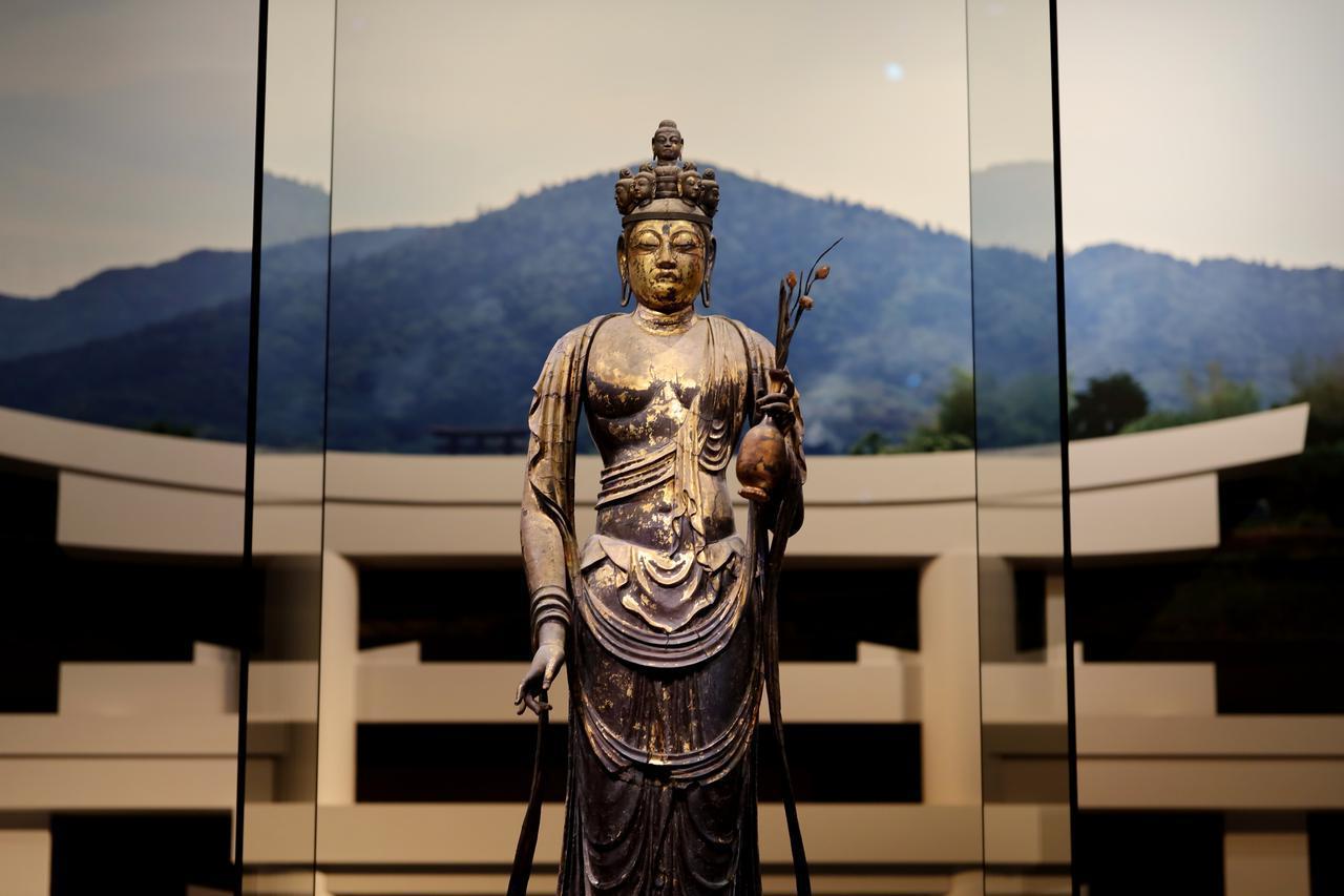 画像: 国宝 十一面観音菩薩立像 (部分) 奈良時代・8世紀 奈良・聖林寺蔵 背景には三輪山の写真と、大神神社の三ツ鳥居の再現