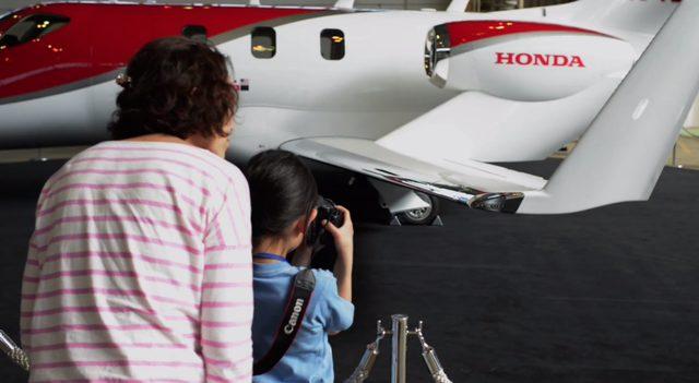 画像: ホンダ初の小型ジェットを撮影する幼い少女。彼女が抱えるカメラはキヤノン。 www.youtube.com