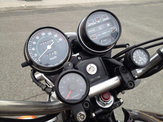 画像: ハンドルバーのクランプにマウントされたレブカウンターと時計は社外アクセサリーです。左は速度計で、右はインジケータと燃料系を収めています。Lレンジは0~100km/hまで、☆レンジは0~160km/hまでが守備範囲であることが文字盤に示されております。ステアリングシャフト上には、この時代の国内モデル特有の装備、赤い速度警告灯が埋め込まれてます。