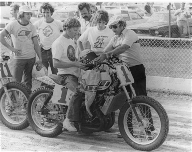 画像: TZ750ダートトラッカーに跨るケニー。ハンチング&サングラスの人物は、ケル・キャラザースです。 images.cyclenews.com