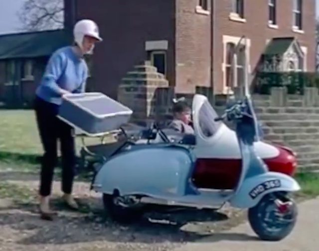 画像: サイドカー付きのスクーターにトランクを積むお母さん。モデルはおそらく、ランブレッタの125 or 150 LIのセコンダ・セリエでしょうか? www.facebook.com