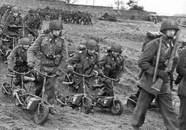画像: ウェルバイクと英国軍兵士たち。戦場という緊迫した場面ですが、ウェルバイクのユーモラスな姿が浮いて見えてしまいます。 s1jzu5hcgojbfje2ba52v9a8.wpengine.netdna-cdn.com