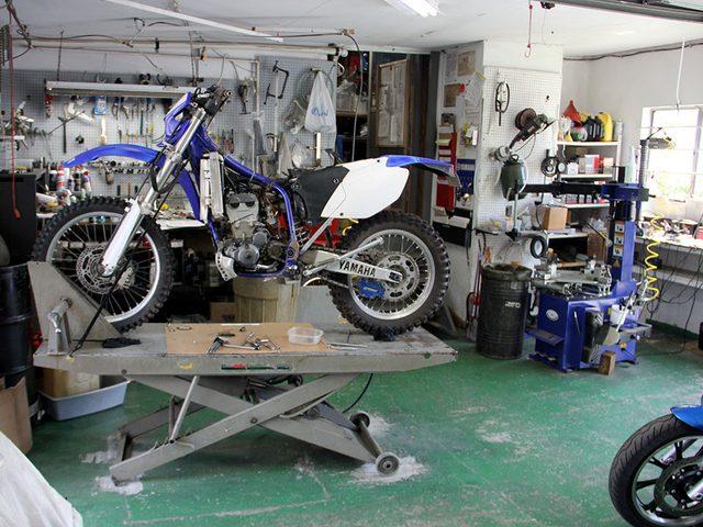 画像: リフトとタイヤチェンジャーを備えるワークショップ。電動工具などの大物も壁面収納してます。 huntermotorcycle.com