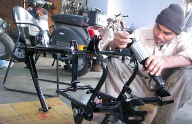 画像: 車体の組み立て開始・・・。ワークショップには多くの鉄スクーター(ベスパ)とかが置いてあり、インドっぽいな〜と思いました(インドはスクーターでプロパンボンベなどを過積載輸送したりするので、剛性のある鉄ボディのスクーターが人気なのです。あと、鉄製のように板金修理ができない樹脂製外装のスクーターが好まれない、という事情も・・・)。 www.youtube.com