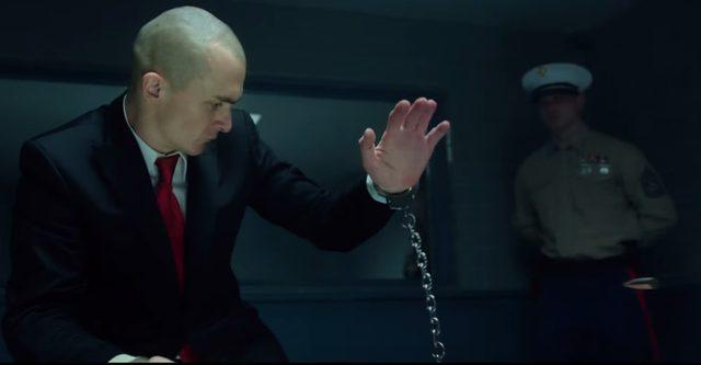 画像: すくっと立ち上がるエージェント47の腕には手錠が・・ www.youtube.com