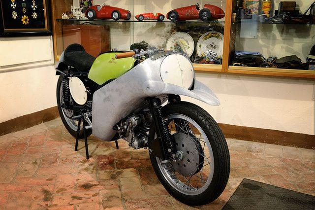 画像: 1954年の350ccクラスを制覇した、ファーガス・アンダーソンの350ビアルベロ(空冷単気筒DOHC2バルブ)。フロントフェンダーを兼ねたこのくちばしが、最初期のエアロ・デバイスと言えるのではないでしょうか? www.motorvalley.com
