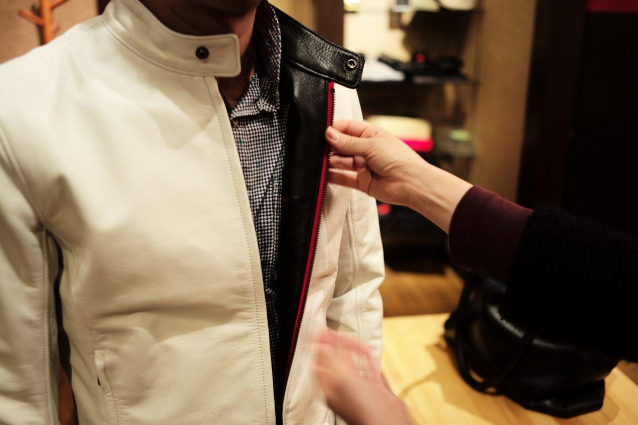 画像: 裏の返しにも黒革を使う。ジッパーは黒だが布地にシンイチロウアラカワのイメージカラーである赤を入れた。 サイドのポケットにも同じように赤を差して、白・黒・赤の鮮やかなコントラストをさりげなく見せる。