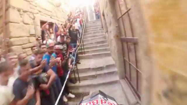 画像: 狭い階段をグングン上ります! 脇には観衆がぎっしり集まっています。 www.youtube.com