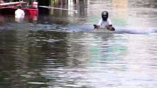 画像: 後ろに乗る人をどこかに運んだのでしょう。今度はライダーひとりで引き返してきます。それにしても、車両もほとんど冠水してますね・・・。 www.youtube.com