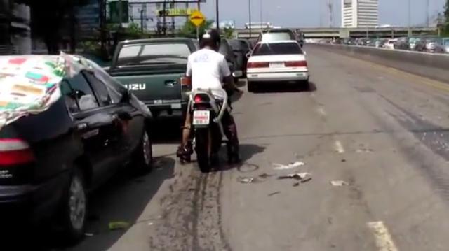 画像: ひと仕事?終えて、水のない高い位置の道路に来たライダーとモーターサイクル。ん?・・・何やらホースのようなものが見えますね? www.youtube.com