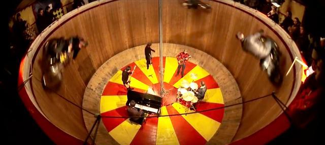 画像: 3台のモーターサイクルがグルグル疾走するなか、熱演を繰り広げるビーディ・アイのメンバーたち・・・。 www.youtube.com