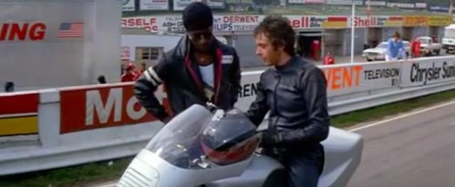 画像: 相棒のサイダー(左)と一緒にシルバードリームレーサーをテストするニック。やがて兄の残したこのマシンで、ニックはこの年の英国GP(シルバーストーン)を走ることを考えるようになります・・・。 www.youtube.com