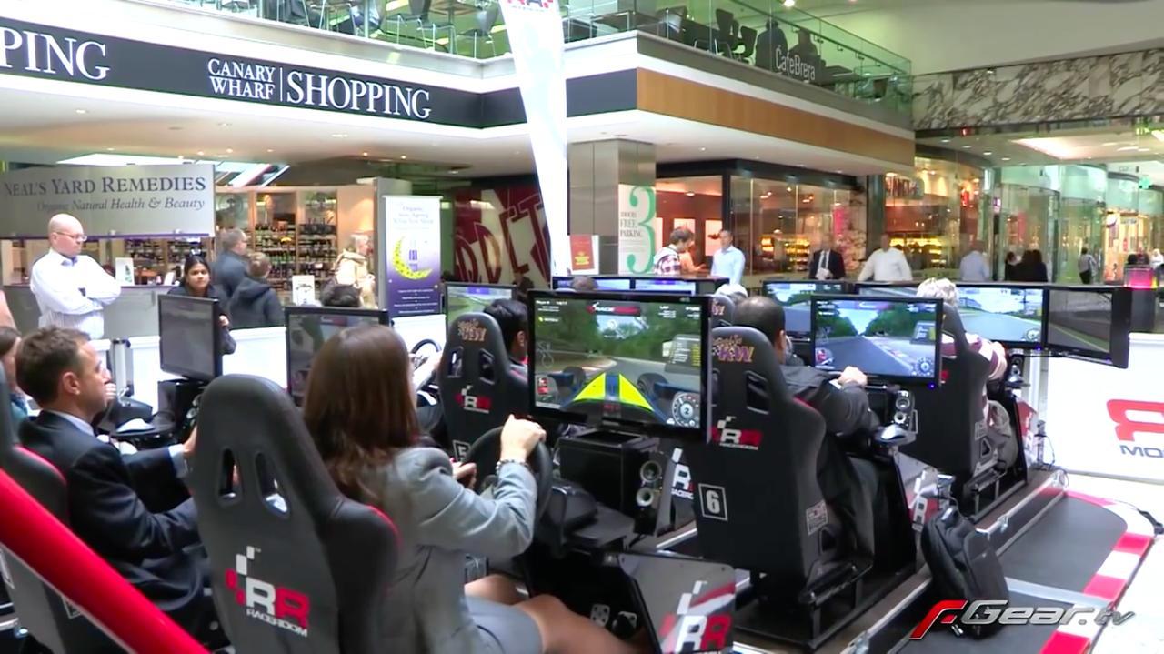 画像: 会場の通路部に設けられた、F1ビデオゲームのコーナー。人々が楽しげにゲームに興じております。 www.youtube.com