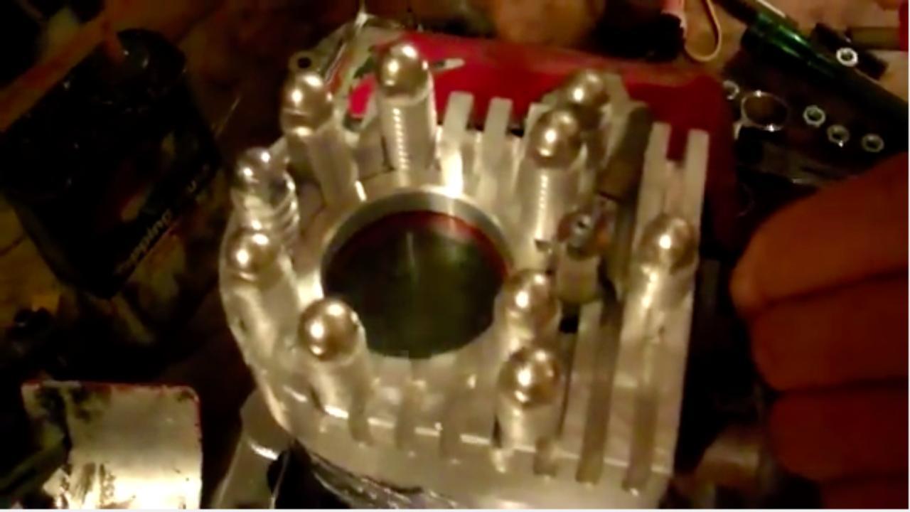 画像: ブリッグス&ストラットンの鋳鉄製の古い4ストローク・サイドバルブ汎用エンジンに、アルミ削りだしのシリンダーヘッドがついています。そしてピストンボアに近いサイズで、耐熱ガラス?が取り付けられています。なおブリッグス&ストラットンは20世紀初頭のアメリカで創業したエンジンメーカーで、日本でもエンジンや芝刈り機などの製品を販売しています。 www.youtube.com