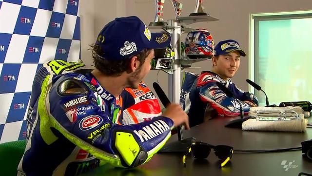 画像: 笑顔はかろうじて?キープしつつも、互いのオーバーテイクに対する意見をぶつけ合う2位のロッシ(手前)と3位のロレンソ(奥)。 www.motogp.com