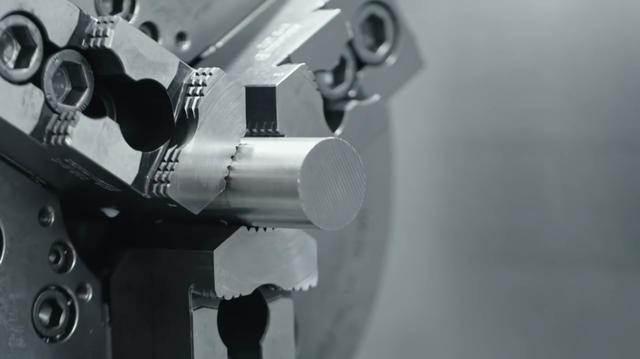 画像: 丸棒が適当なサイズにカットされ、加工機のチャックにくわえられます。 www.youtube.com
