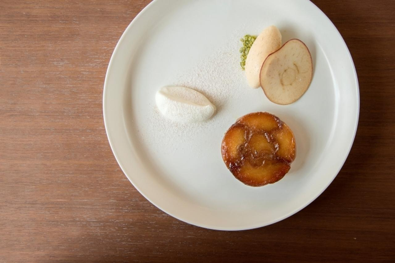 画像: 山田農園の「百年紅玉」を使ったタルト・タタン 1,800 yen ( tax incl. ) 5月に訪れた青森からは、山田農園の樹齢百数十年を超える木になる「百年紅玉」が届きました。水分量が控えめで、香り高く、酸味が効いている種類で、タルト・タタンを作るために生まれたような素晴らしいりんごです。素材の持ち味を生かす自慢のタルト・タタンです。 prtimes.jp