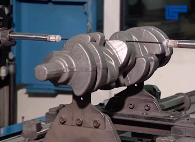 画像: 熱間鍛造を終えたクランクシャフトの寸法が正確に仕上がっているか、計測する場面です。 www.youtube.com