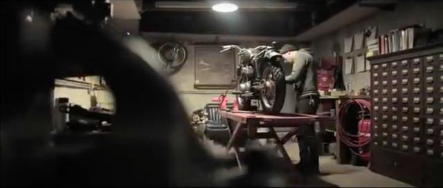 画像: ワークショップの作業リフトの上の、クラシック・モーターサイクルと対話するように整備に励む男・・・。 www.youtube.com