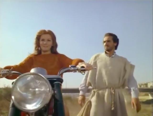 画像: 世捨て人の主人公(右・ヴィットリオ・ガスマン)と並び、歩くスピードでV7を操るアン=マーグレット。 www.youtube.com