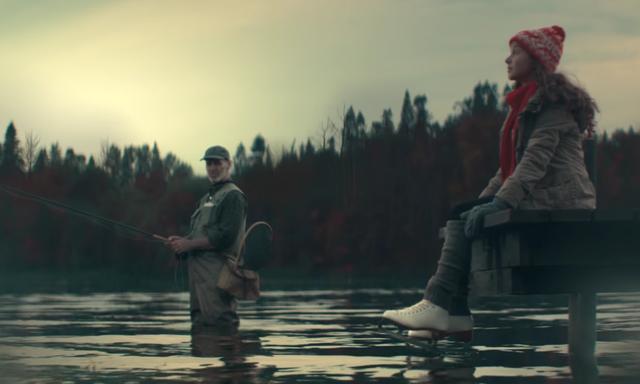 画像: スケート靴を履いて、湖が凍るのを待っている少女の横で、釣りに興じるおじさんは怪訝顔 www.youtube.com