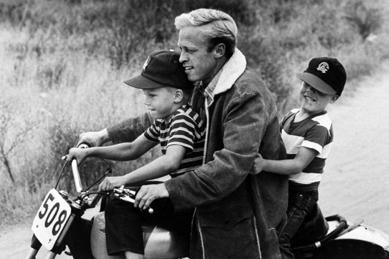 画像: 1971年に公開された、「On Any Sunday」撮影中のひとコマ。子供たちと楽しくモーターサイクルに3人乗りするブルース・ブラウン。 racerxonline.com