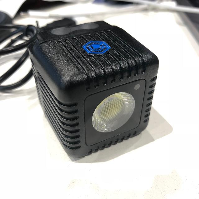 """画像: 44MM 角の立方体 重量 105G LED 1500 ルーメン CRI 80-85 750 LUX(1M) IP68(メーカー公表値水深 30M) 底部に 1/4""""ねじ穴 USB ケーブルを経由しての再充電 BLUETOOTH 使用可能 ビデオモード 50%の使用で約 2 時間作動 GOPRO およびアクションカメラを簡単に搭載 安定的なライトとフラッシュモード カメラとのスレイブ機能 堅牢なボディ スマートフォンのアプリによるリモートコントロール 初のモバイルフォト用オフカメラフラッシュ マルチライトをシンクロおよび同時コントロール クイック充電 色温度 6000K IPHONE、ANDROID に対応 ボタンを使用してマニュアル操作も可能"""