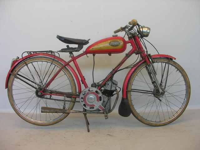 画像: 紆余曲折はあるのですが省略します(笑)。こちらの原動機をつけたモデルは、イタリアのドゥカティの第一号機となったクッチョロ=子犬です。この手の第二次大戦後の原付自転車は2ストロークが多かったのですが、クッチョロは4ストローク単気筒を採用する点が大きな特徴でした。 it.wikipedia.org